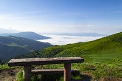 Banco de madera contra el valle de la montaña con el cielo azul claro fotografía de archivo