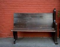 Banco de madera contra la pared de ladrillo roja Fotografía de archivo