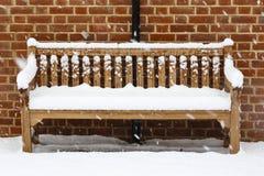 Banco de madera cubierto en nieve fotografía de archivo