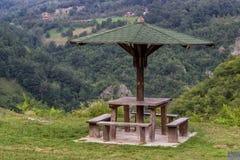Banco de madera del asiento con la tabla en naturaleza debajo del paraguas de madera Foto de archivo
