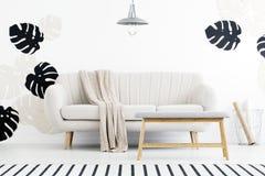 Banco de madera delante del sofá con la manta debajo de la lámpara en f blanca foto de archivo
