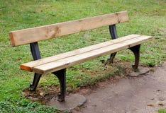 Banco de madera en el parque en hierba Imagen de archivo