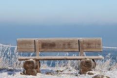 Banco de madera en la costa delantera del mar Báltico en invierno fotos de archivo