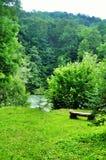 Banco de madera en la orilla de un río de la montaña Fotografía de archivo