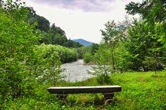 Banco de madera en la orilla de un río de la montaña Imagen de archivo libre de regalías