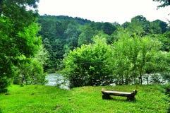 Banco de madera en la orilla de un río de la montaña Fotos de archivo libres de regalías