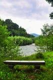 Banco de madera en la orilla de un río de la montaña Fotografía de archivo libre de regalías