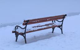 Banco de madera en un día nevoso por el lago congelado Imagen de archivo
