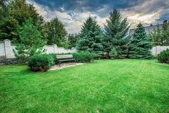 Banco de madera en un jardín hermoso del parque Fotografía de archivo libre de regalías