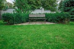 Banco de madera en un jardín hermoso del parque Fotos de archivo