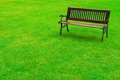 Banco de madera en un parque herboso imagenes de archivo