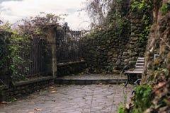 Banco de madera en un parque piedra-construido imagenes de archivo