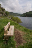 Banco de madera que pasa por alto un lago Imagen de archivo
