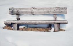Banco de madera rústico viejo rodeado por las porciones de nieve Imagen de archivo