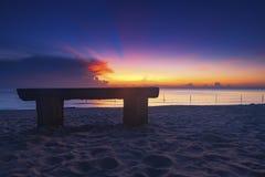 Banco de madera sobre la playa tropical hermosa y el fondo crepuscular mágico de la salida del sol Imagen de archivo