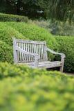 Banco de madera vacío de Brown que se sienta en el medio de los setos del jardín Foto de archivo