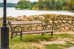 Banco de madera y del hierro cerca de la orilla del lago Fotos de archivo libres de regalías
