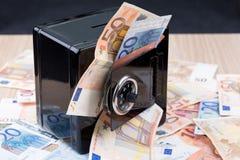 Banco de moneda negro del metal con el dinero Imágenes de archivo libres de regalías