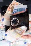 Banco de moneda negro del metal con el dinero Imagen de archivo