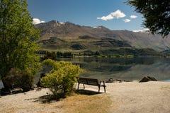 Banco de parque com reflexões da montanha no lago fotos de stock