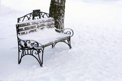 Banco de parque del vintage en la nieve al lado de un árbol imagen de archivo