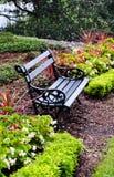 Banco de parque do ferro cercado por flores Imagens de Stock