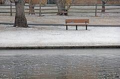 Banco de parque por la charca en nieve del invierno Imagen de archivo