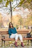 Banco de parque rasgado sonriente del otoño del sombrero negro de los vaqueros del adolescente que se sienta hermoso joven Foto de archivo
