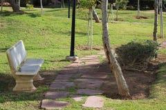 Banco de pedra branco no parque imagens de stock