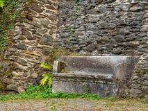Banco de piedra antiguo a lo largo de una pared del castillo fotos de archivo