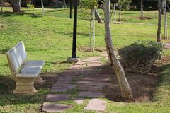 Banco de piedra blanco en el parque imagenes de archivo