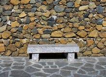 Banco de piedra contra la pared de piedra Fotos de archivo