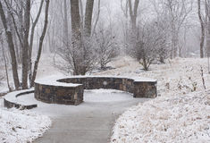Banco de piedra en un parque en el invierno fotografía de archivo