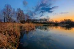 Banco de um lago no inverno durante o por do sol foto de stock