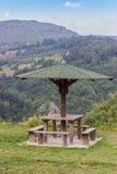 Banco del asiento con la tabla en naturaleza debajo del paraguas de madera Imagen de archivo