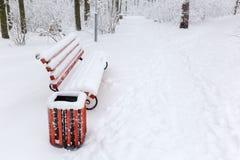 Banco del giardino coperto di neve sul vicolo in parco nevoso fotografie stock libere da diritti