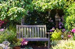 Banco del giardino nella fioritura di primavera immagini stock libere da diritti