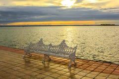 Banco del hierro en la costa en la puesta del sol Fotos de archivo