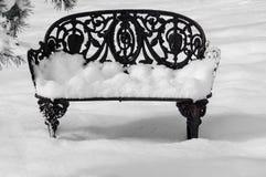 Banco del jardín del hierro labrado en la nieve Imágenes de archivo libres de regalías