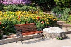 Banco del jardín en el fondo colorido de la imagen de la flor del parque fotos de archivo libres de regalías