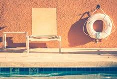 Banco del verano y tubo del rescate por la piscina imagen de archivo