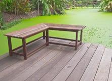 Banco di legno ad angolo retto sulla veranda accanto allo stagno verde della lemma Fotografie Stock Libere da Diritti