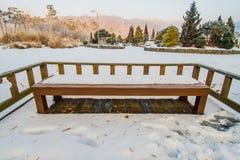 Banco di legno coperto dentro di parco pubblico Fotografia Stock Libera da Diritti