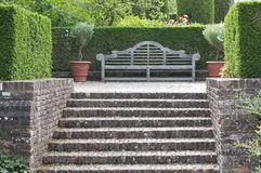 Banco di legno del giardino in giardino inglese Fotografia Stock