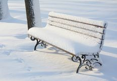 Banco di legno del parco dopo la bufera di neve Fotografia Stock