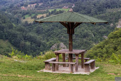 Banco di legno della disposizione dei posti a sedere con la tavola in natura sotto l'ombrello di legno Fotografia Stock