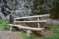 Banco di legno lungo le rocce Fotografia Stock