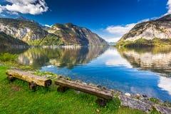 Banco di legno nel lago della montagna nelle alpi Fotografie Stock Libere da Diritti