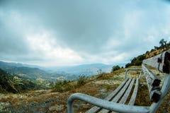 Banco di legno nella valle della montagna immagine stock