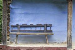 Banco di legno sulla vecchia casa blu dell'azienda agricola immagine stock libera da diritti